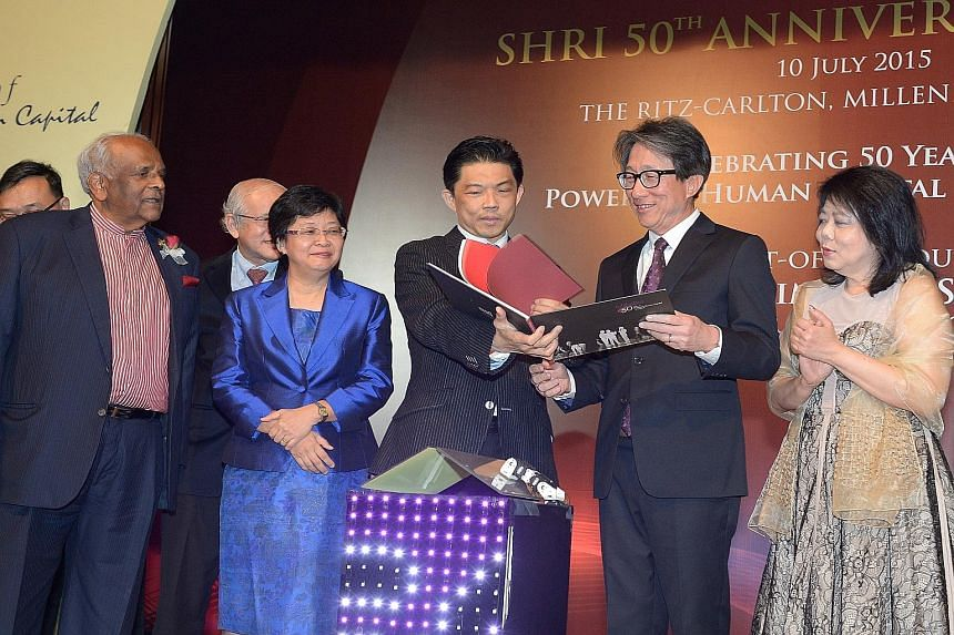 SHRI president Erman Tan showing Manpower Minister Lim Swee Say a book chronicling the institute's history. SHRI, set up in 1965, yesterday celebrated its 50th anniversary.