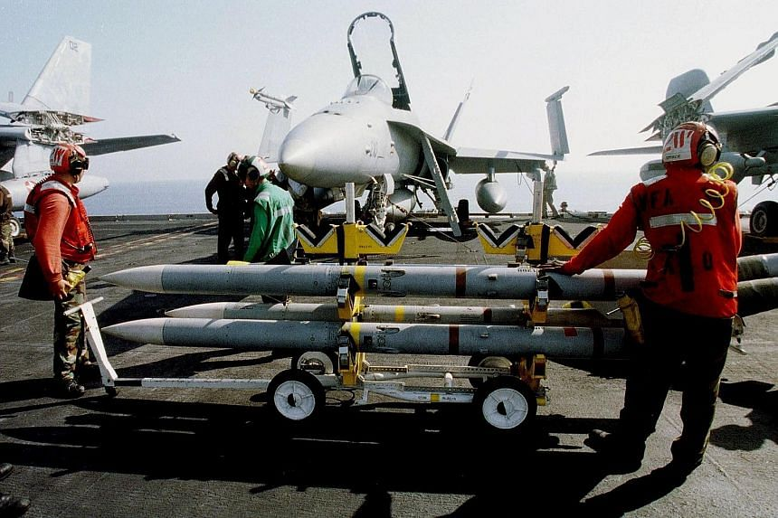 Crewmen handling SeaSparrow rockets on board a US aircraft carrier. The 12-country Nato consortium oversees development and shares the costs of the SeaSparrow missile, an advanced ship-borne weapon that is designed to destroy anti-ship sea-skimming m