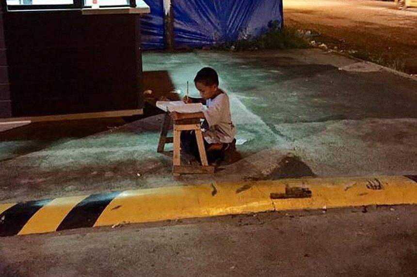 Daniel, pictured with his mother, Ms Christina Espinosa, has been overwhelmed with aid after a photo of him (right) studying on the pavement by the light of a McDonald's outlet went viral on the Internet.