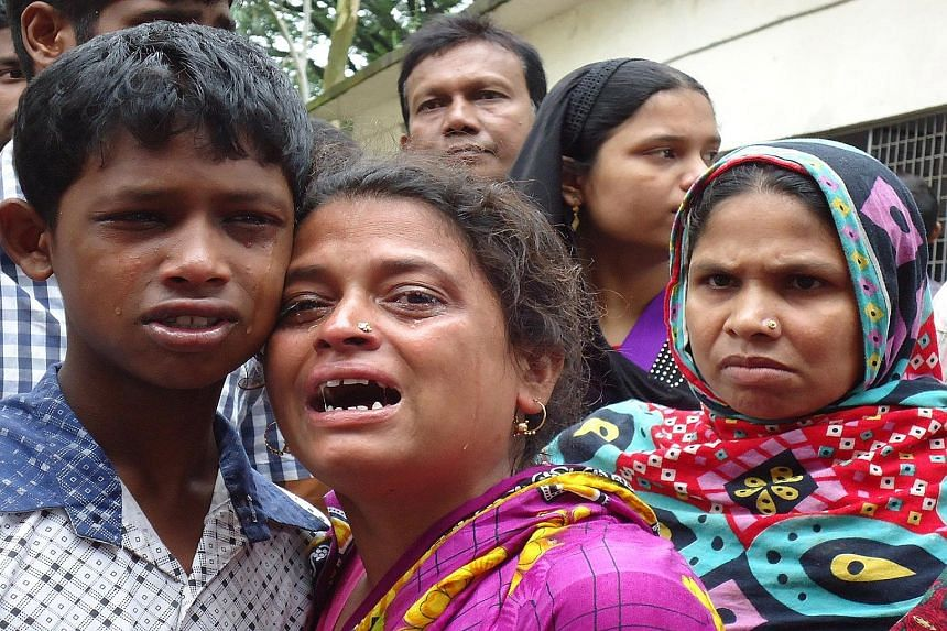 Relatives of victims of the stampede in Bangladesh's northern city of Mymensingh grieving over the loss of their loved ones yesterday. There were two children among the dead. Most of the others were poor and emaciated women.