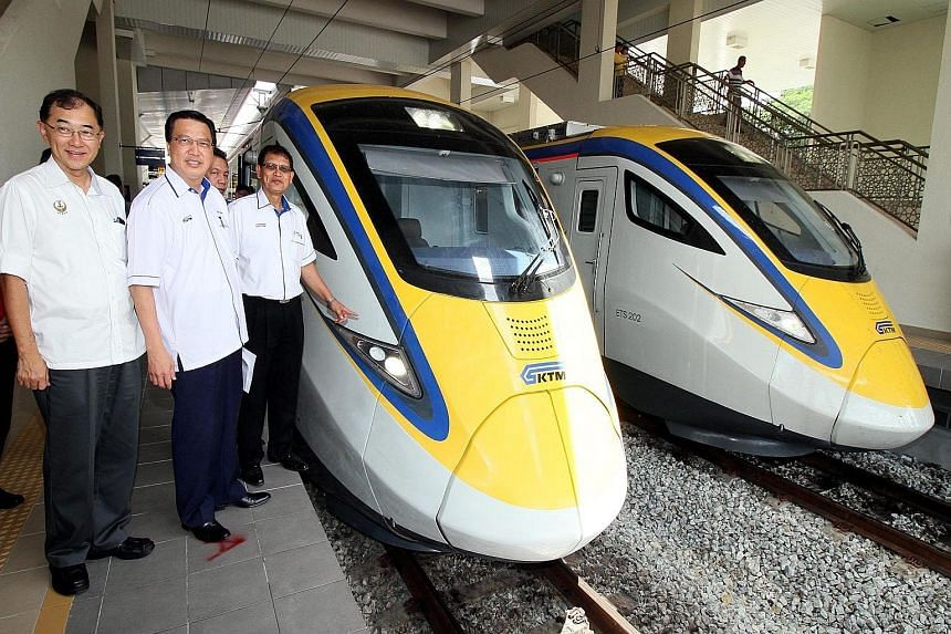 (From left) Perak state executive council member Mah Hang Soon and Malaysian Transport Minister Liow Tiong Lai join KTM president Sarbini Tijan as he checks out the new electric trains.