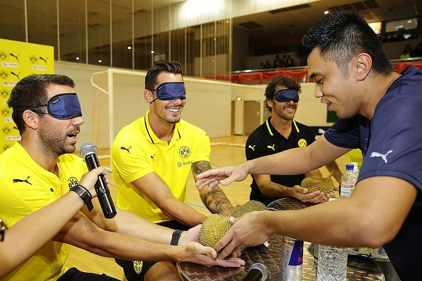Above: Time to meet the king of fruits at Nanyang Polytechnic, as Dortmund's (from left) Gonzalo Castro, Roman Burki and club legend Karl-Heinz Riedle have their first feel of durian blindfolded. Right: Over at 313@Somerset, Dortmund players (from le