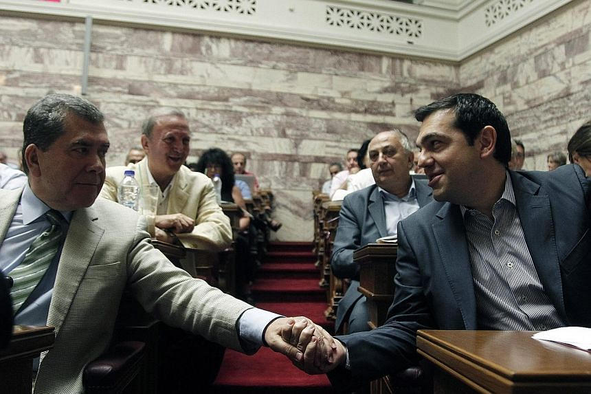 Greek Prime Minister Alexis Tsipras greeting a lawmaker (far left) from his Syriza party in the Greek Parliament in Athens yesterday.