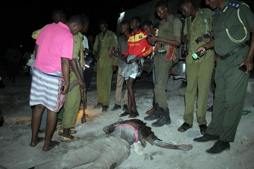Somali army soldiers stand around the body of a killed militant.