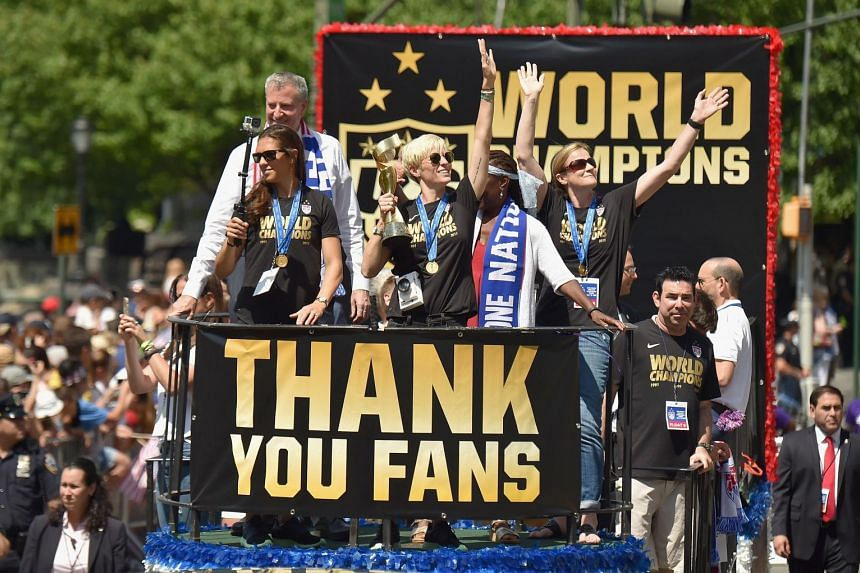 The US women's soccer players show off their trophy, as New York welcomed them home after their World Cup win.