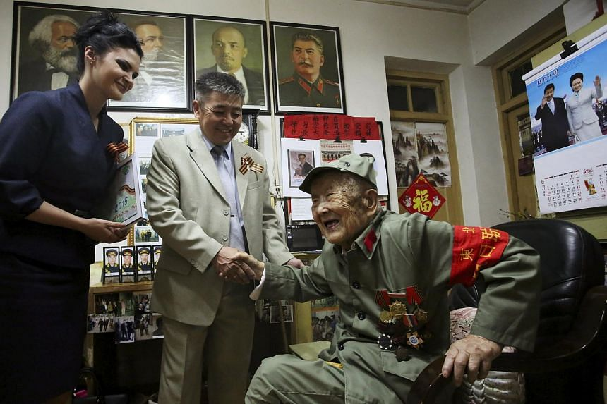 Lu Baoping, a 97-year-old Chinese veteran who fought against Japan during WWII, shaking hands with a Russian diplomat as he receives a commemorative medal marking the 70th anniversary of the end of the war.
