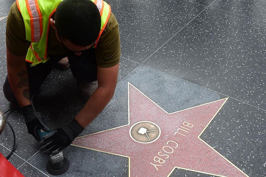 "A worker cleaning Bill Cosby's Star on the Hollywood Walk of Fame in this 2014 photo, after it was reportedly vandalised the night before with the word ""rapist"" written multiple times."