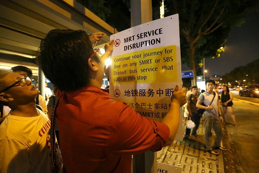 SMRT staff putting up a train disruption notice at a bus stop outside Lavender station on July 7.