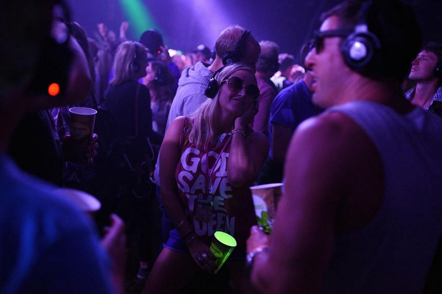 Revellers listening to music in their headphones during a silent disco at the Glastonbury music festival.