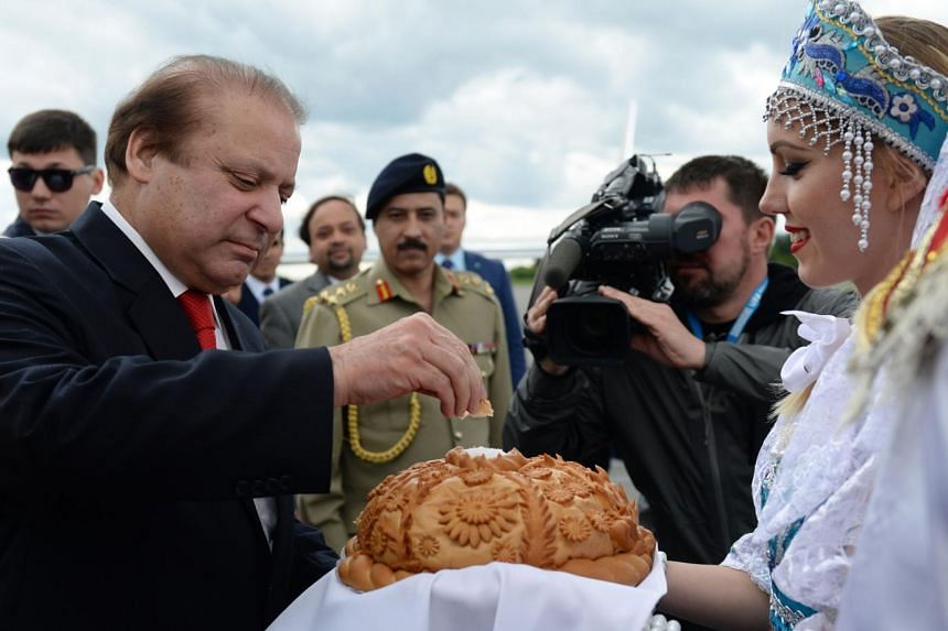Pakistan PM Nawaz Sharif (left) tastes traditional bread during a welcome ceremony in Ufa.