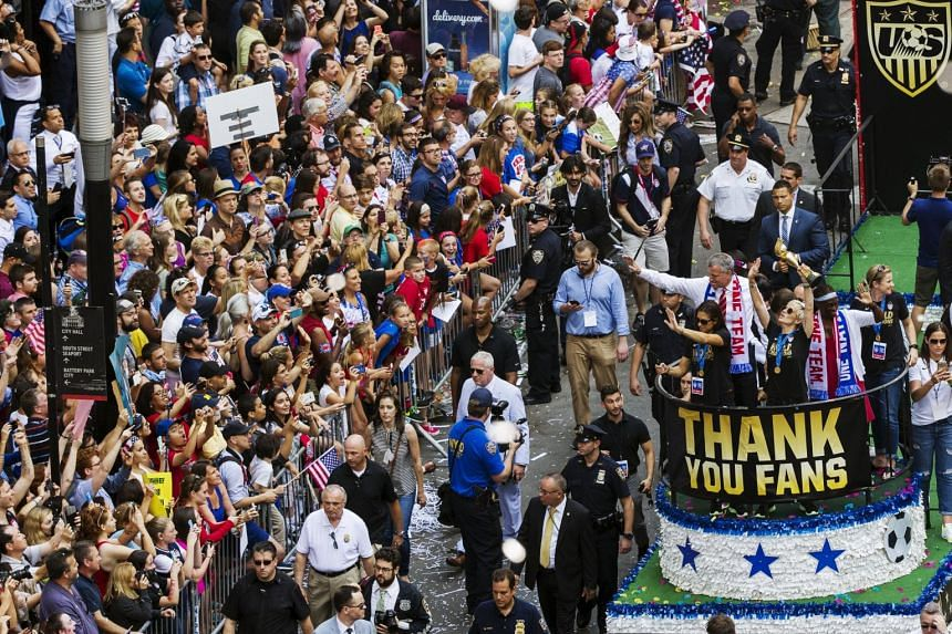 Megan Rapinoe (centre) of the US women's national team holds the World Cup aloft as fans cheer.
