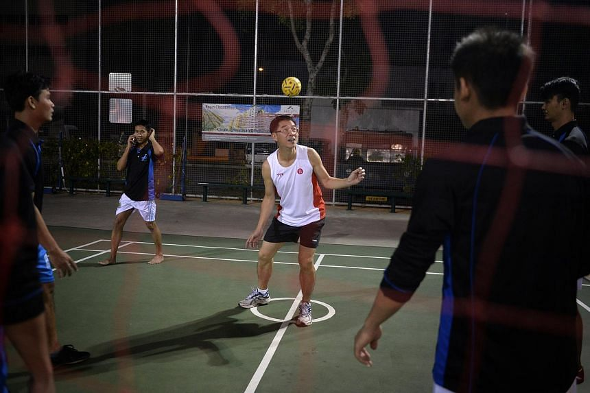 """Dr Tan Lai Yong playing sepak takraw with Myanmar workers at a dormitory. Known as the """"wandering saint"""" of Singapore, the medical doctor lives a spartan life and has been praised for his ideas to better society."""