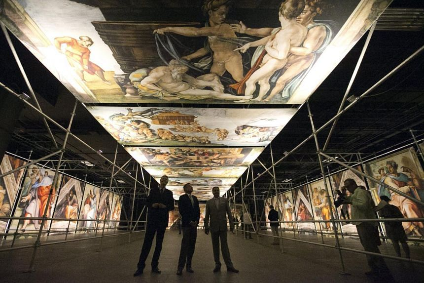 Visitors to the exhibition of the photos of the Michelangelo frescoes can photograph them at a distance not allowed in the Sistine Chapel.