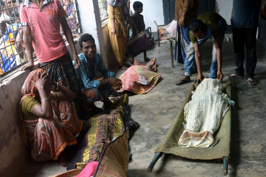Bangladeshi relatives sit near the bodies of some of those killed in the stampede.
