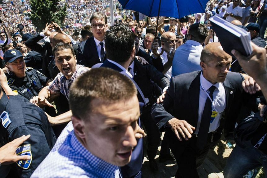 Bodyguards try to protect Serbian Prime Minister Aleksandar Vucic (third left, with glasses).