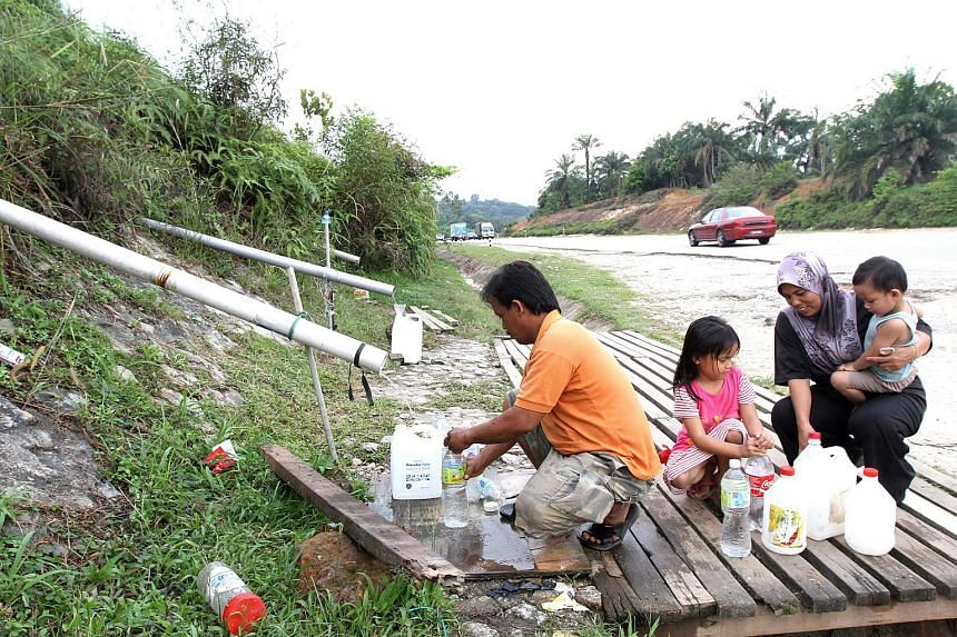 A family collecting spring water in Puncak Alam due to the water crisis in the Klang Valley.