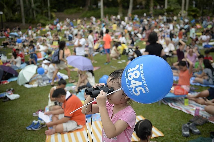 Six-year-old Claire Shen making sure she did not miss anything at The Straits Times 170th anniversary concert at the Botanic Gardens yesterday.
