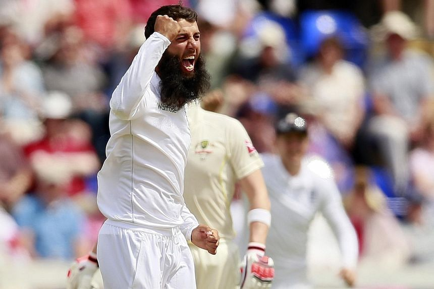 England's Moeen Ali celebrates after taking the wicket of Australia's David Warner.