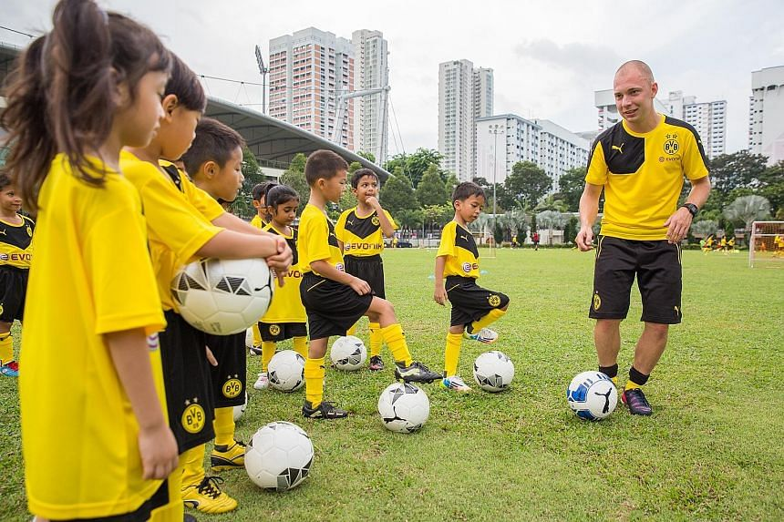 Some 60 children aged five to 12 took part in an hour-long football clinic organised by German Bundesliga club Borussia Dortmund's youth-team coaches yesterday morning. The event, held at the People's Association headquarters, was organised by chemic