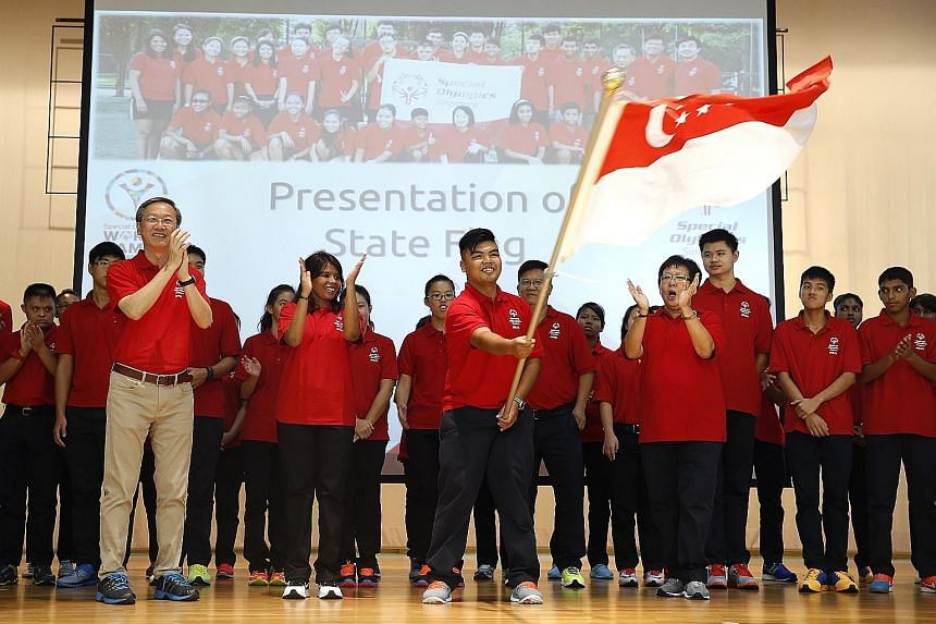 Table-tennis player Nor Safik Nor Mohd Bahtiar waves the national flag at a send-off ceremony attended by Minister of State Sam Tan.