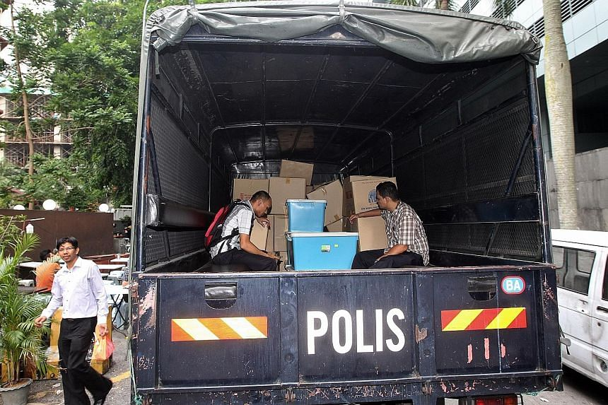 Officers from the special task force with boxes and computer hardware taken from 1MDB's headquarters last Wednesday. Part of its work is to look into the bank accounts of Prime Minister Najib Razak.