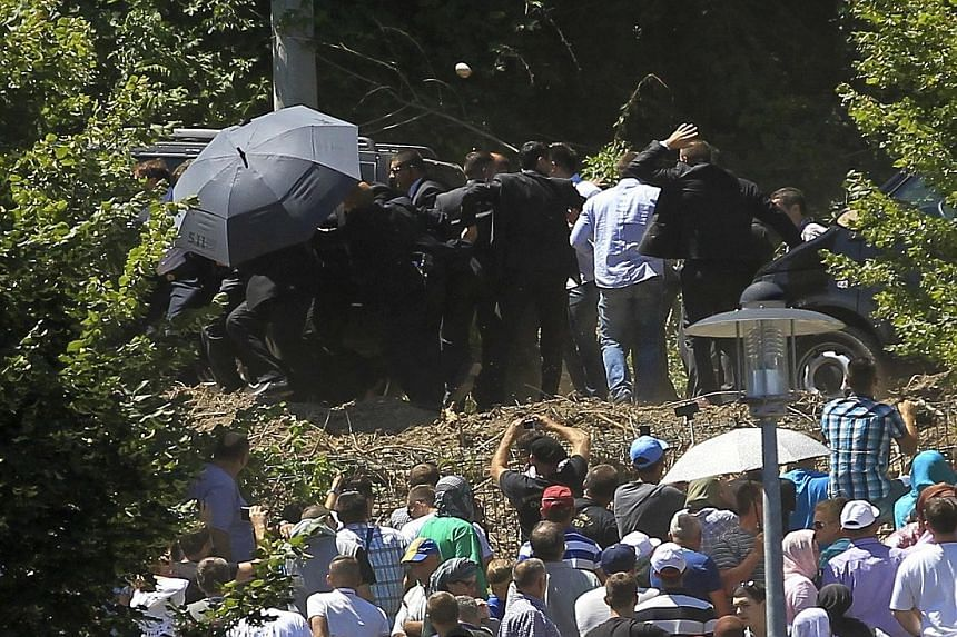 Bodyguards shielding Serbian Prime Minister Aleksandar Vucic from a crowd throwing stones and bottles at the ceremony marking the anniversary of the Srebrenica massacre. About 8,000 men and boys were executed there by Bosnian Serb forces in 1995.