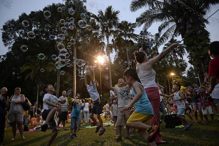 Commemorative gifts, such as ST170 picnic mats (above) and balloons, such as those held by six-year-old Nina Miao (left), were given out in the evening to the audience, who enjoyed a fine performance by the Singapore Symphony Orchestra (below), which
