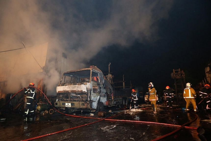 SCDF officers work to bring the fire under control.