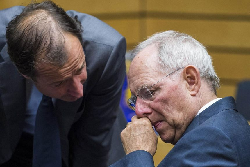 German Finance Minister Wolfgang Schaeuble confers with an unidentified official.