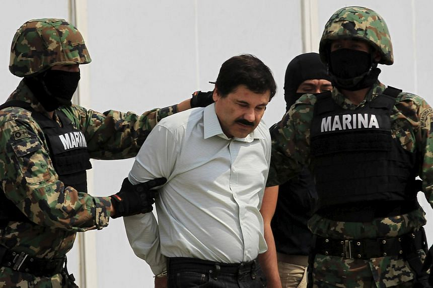 """Mexican drug lord Joaquin """"El Chapo"""" Guzman (centre) is escorted by soldiers during a presentation at the Navy's airstrip in Mexico City on Feb 22, 2014."""