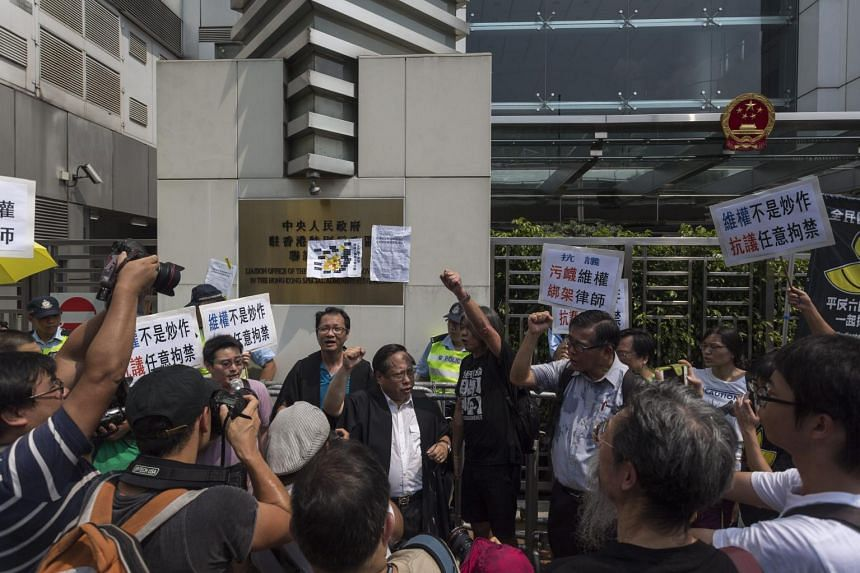 Activists with the Hong Kong Alliance in Support of Patriotic Democratic Movements of China ask for the release of retained human rights activists and lawyers during a protest outside the Liaison Office of the Central People's Government in Hong Kong