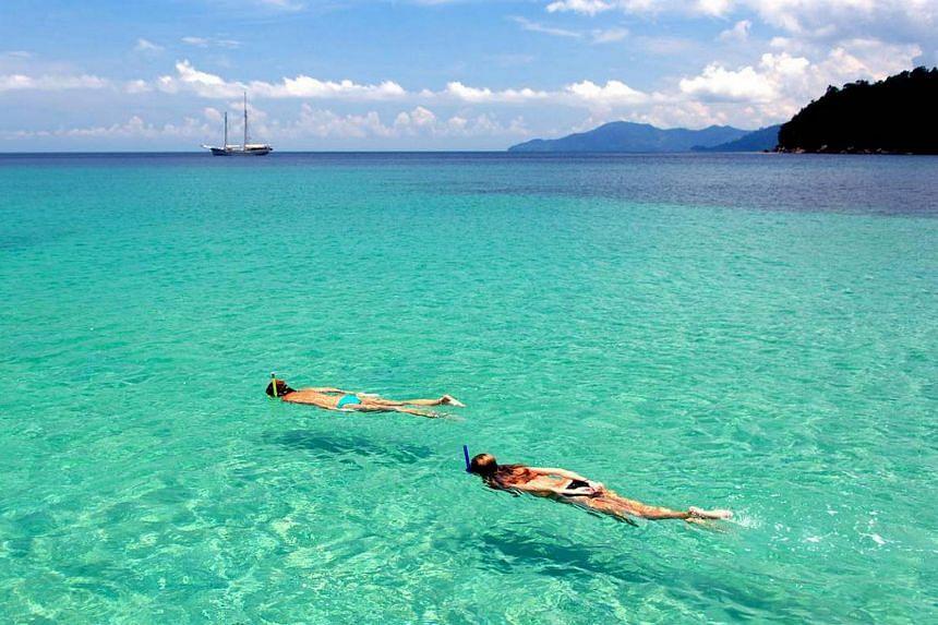 Guests of the Raja Laut (behind) snorkelling in crystal clear waters in Myanmar's Mergui Archipelago.