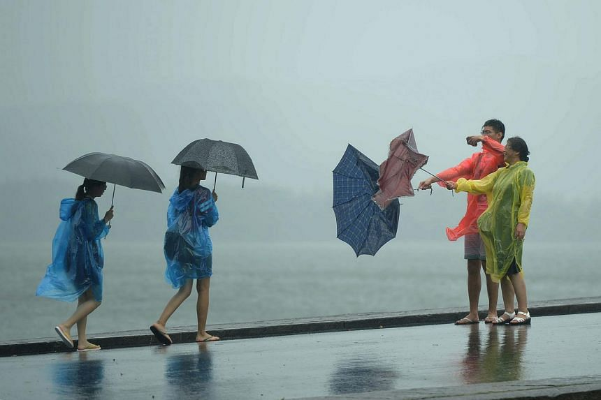 Tourists take photos of their inside-out umbrellas in the West Lake scenic zone in Hangzhou, east China's Zhejiang province.