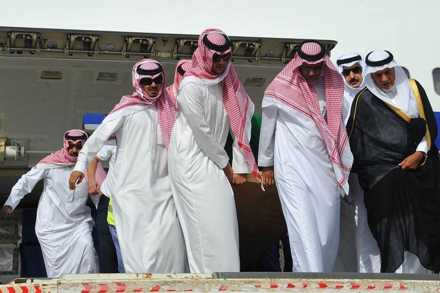 Saudi Prince Turki al-Faisal (right) stands next to the coffin as it is unloaded from a plane upon arrival in Jeddah, a few hours before the funeral.