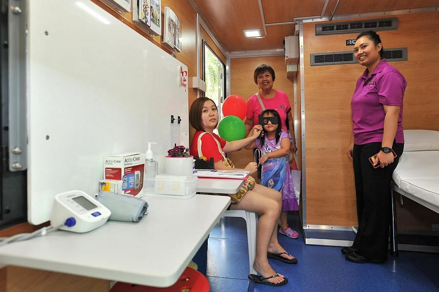 Chloe Huang having her eyes checked inside the Wellness Bus at The Serangoon Community Club on July 12, 2015. Accompanying her is her mother Pauline Tan (far left) and grandmother Lee Kim Hong.