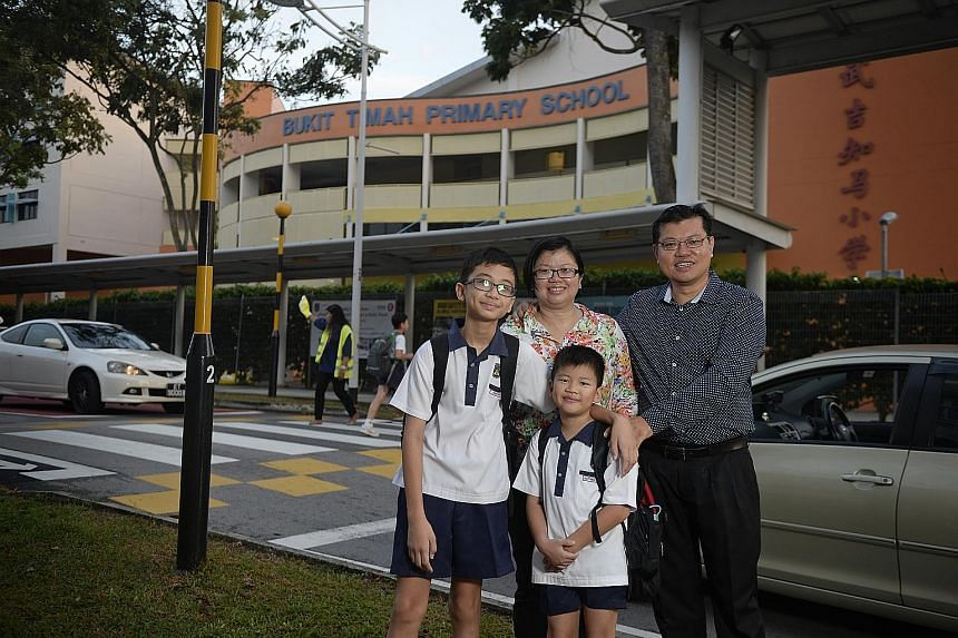 """Madam Chua Huay Wen, 39, her husband Kenneth Seah, 43, and their children Jonathan (left), 11, and Matthew, eight, outside Bukit Timah Primary School, which sits among private estates and """"brand-name"""" schools such as Pei Hwa Presbyterian and Methodis"""