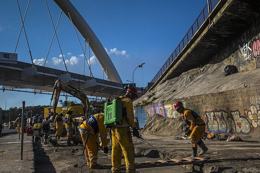 """Workers at a Brazil Rapid Transit construction site in Rio de Janeiro's Brasil Avenue. Singapore companies can share their infrastructure concepts with Latin America as the region has a """"$170 billion infrastructure gap"""", says IE Singapore's divisiona"""