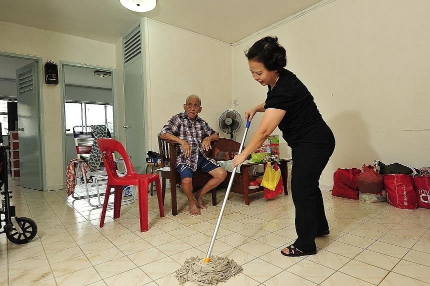 Ms Noriza A. Mansor mopping the floor of Mr Tan Soy Yong's flat. She spends at least six hours a week helping him.