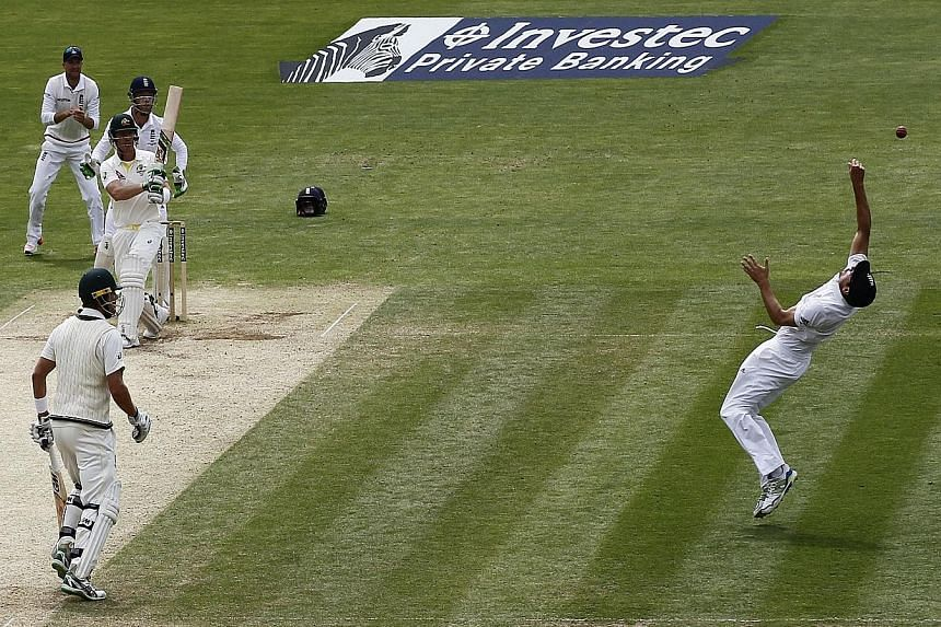 England captain Alastair Cook (right) makes a stunning catch to take the wicket of Australia's Brad Haddin during the fourth day of the opening Ashes cricket Test. The hosts' emphatic 169-run win laid bare the problems with the visitors' batting and
