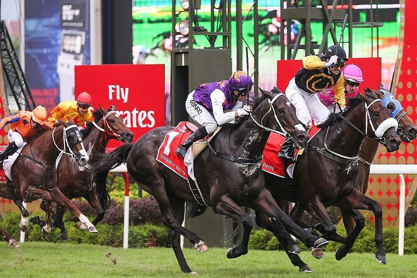 Jockey Corey Brown (in yellow and black silks) salutes the Kranji crowd as Quechua is first past the post at the Emirates Singapore Derby.