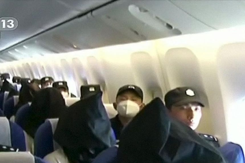 People being deported from Thailand seated in an airplane while flanked by police at an unidentified location in China.