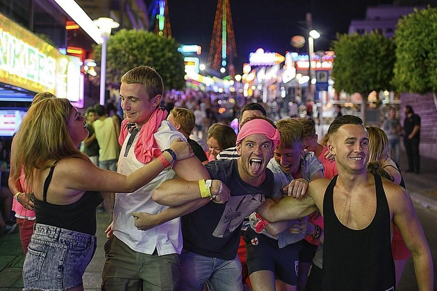 People along a neon-lit stretch of Magaluf, in Mallorca, Spain, last month. The mayor says rowdy tourist behaviour has led to a backlash among residents. Officials in popular tourist destinations from Spain to Malaysia are starting to take steps agai
