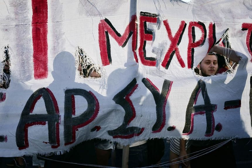 Protesters opposing austerity measures stand behind a banner during an anti-EU demonstration in Athens.