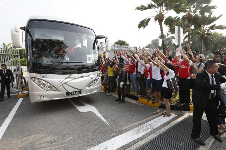 Fans of Arsenal trying to take pictures of the players as they leave Changi Airport in the team bus on Monday, July 13, 2015.