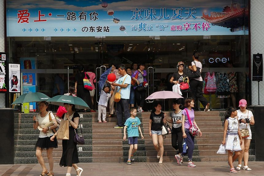 Shoppers and tourists come out of a shopping centre in Beijing, China.