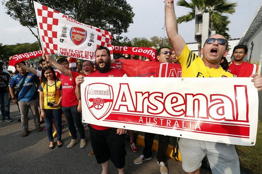 Arsenal fans welcoming the players after the team touched down in Singapore on July 13, 2015. The Premier League team will be taking part in the Barclays Asia Trophy tournament.