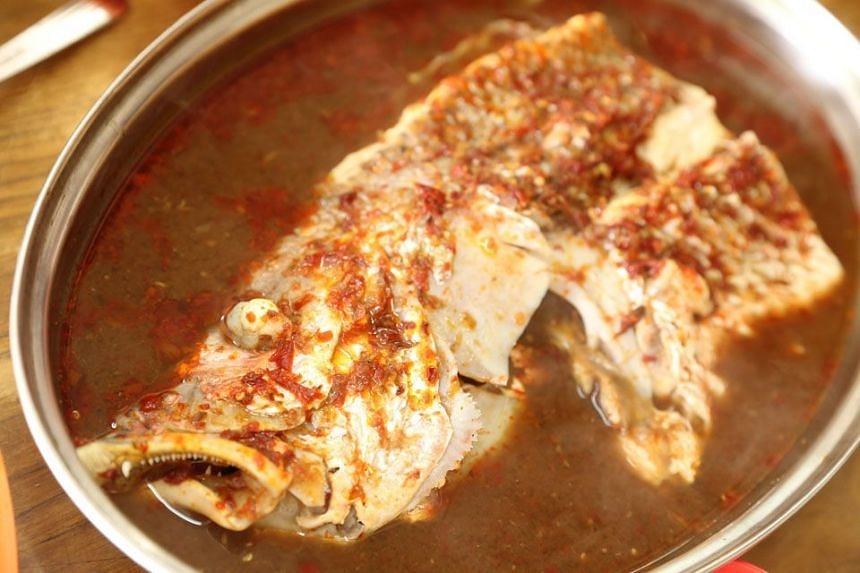 KLUANG INSTITUTIONS: Restoran Ikan Asam Pedas' fish head simmers in a power-packed gravy of spicy tamarind goodness.