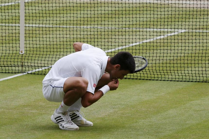 Djokovic eating the grass from centre court after his win.