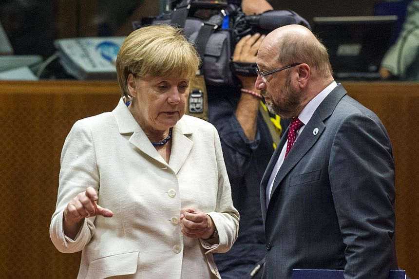 German Chancellor Angela Merkel (left) confers with European Parliament President Martin Schulz prior to the start of a Eurozone summit in Brussels.