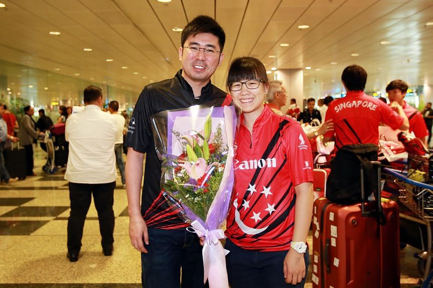 Singaporean bowler Joey Yeo (right), who won the inaugural Bowling World Open in Japan, standing with her coach Remy Ong at Changi Airport after she returned to Singapore.